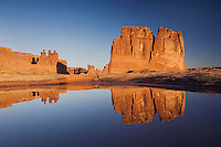 Courthouse Towers at sunrise with reflection in pot hole, Arches National Park, Utah, USA