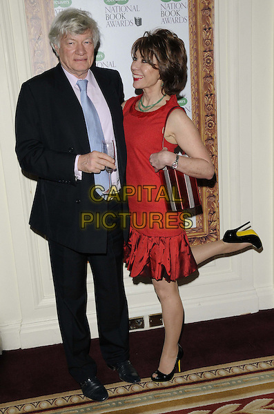 Geoffrey Robertson & Kathy Lette .The 2012 Specsavers National Book Awards, Mandarin Oriental Hyde Park Hotel, Knightsbridge, London, England..December 4th, 2012.full length black red dress leg foot up blue tie suit married husband wife .CAP/CAN.©Can Nguyen/Capital Pictures.