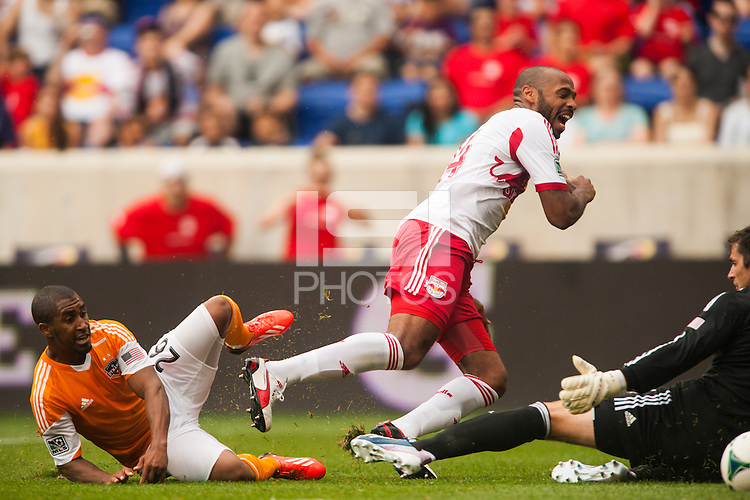 Thierry Henry (14) of the New York Red Bulls goes down in pain after a tackle by Corey Ashe (26) of the Houston Dynamo. The New York Red Bulls defeated the Houston Dynamo 2-0 during a Major League Soccer (MLS) match at Red Bull Arena in Harrison, NJ, on June 30, 2013.