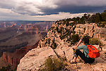 A hiker rests while taking a photograph of the view from the Rim Trail along the Grand Canyon.