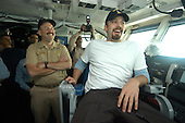 Aboard USS Enterprise (CVN 65), Commanding Officer Captain Eric C. Neidlinger, left, shares a laugh with Academy Award winning actor Ben Affleck, who enjoys the view from the Captain's chair during a tour of the shipís bridge.  Affleck was aboard the nuclear powered aircraft carrier kicking off a United Service Organization (USO) sponsored tour of the Arabian Gulf.  .Mandatory Credit: Milosz M. Reterski - U.S. Navy via CNP    .
