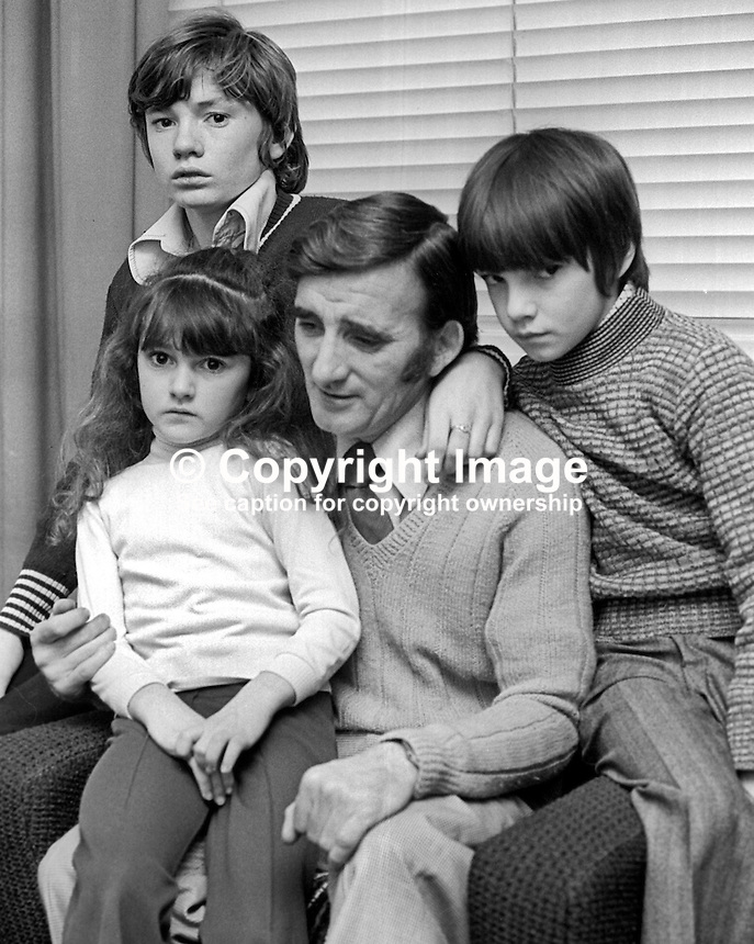 The husband and three of the family of eight of Mrs Chrstine Hughes, of Mountainview Parade, Belfast, who was shot dead 21st December 1975. .Copyright Image from Victor Patterson, 54 Dorchester Park, Belfast, United Kingdom, UK. The attack, attributed to the UDA was carried out by two masked men. There was some suggestion that the target was her husband, Frederick Hughes, who was the manager a social club in the Ardoyne.  Mistaken identity may have been a possibility as Mrs Hughes was dressed  for painting wearing his slacks and a pullover. The children in the photo, Frederick, 13 years, Martin, 10 years, and Kathleen, 7 years, were in the house at the time of the attack. 197512220781..For my Terms and Conditions of Use go to http://www.victorpatterson.com/Victor_Patterson/Terms_%26_Conditions.html