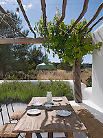 A peaceful al fresco dining area with wooden trestle table and a built-in bench under a rustic wooden pergola