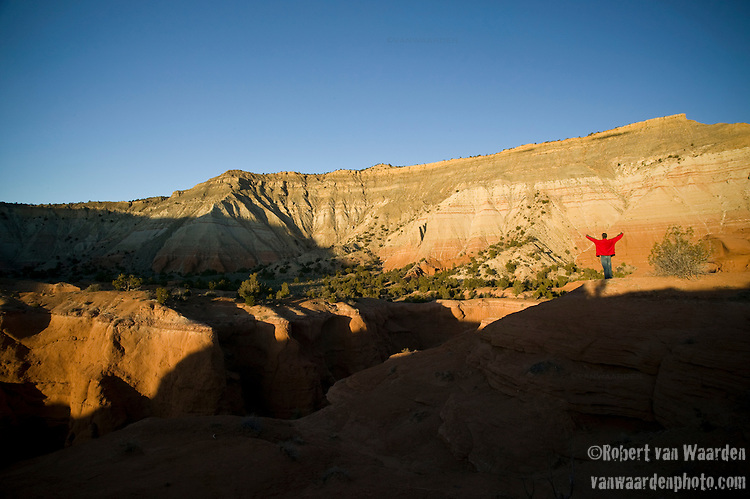 A man in a red jacket spreads his arms and greets the setting sun on the hills of Kodachrome State Park, Utah, United States of America.