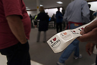 A poll workers hands out stickers to voters at a Columbus, Ohio, early voting center on the first day of early voting in the state..
