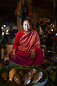 India - Manipur - Imphal - Soibam Lalita, 70 years old. From Kha-Naorem Leikai, near Manipur UniversityThe fish comes from Loktak Lake. (She sells catfish and golden carp). (Those cutting the fish are among the few men allowed into the market.  They are unemployed youths. She has been selling fish for 35 years. Her business is very good, with the profits she has given education to all her 4 kids. In a month she earns 60,000 rupees, sometimes it's more. It has been managed by women since generations, we wouldn't feel comfortable with men. If men are around, we are not free to talk, among women they share stories.
