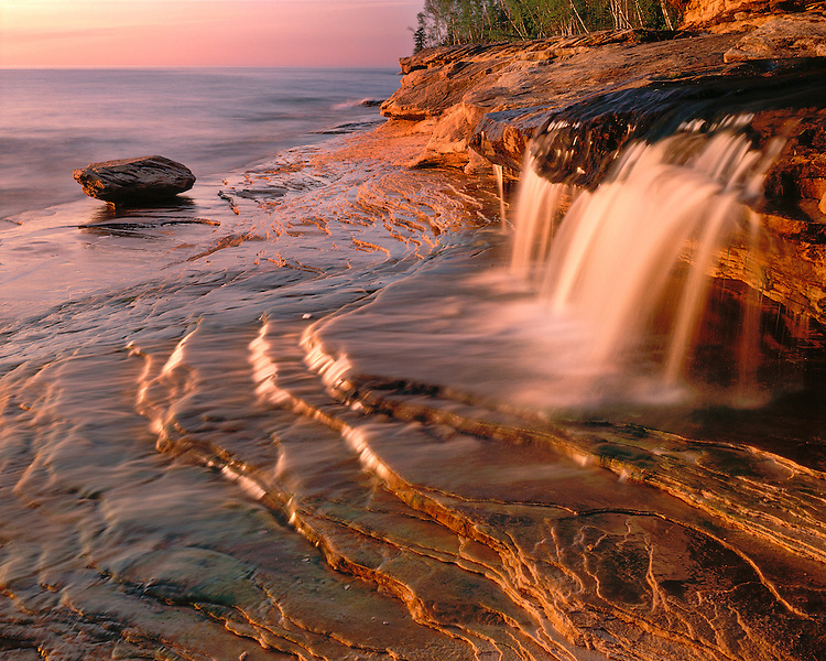 Sunset light on a waterfall on the shore of Lake Superior at Miners Beach; Pictured Rocks National Lakeshore, MI