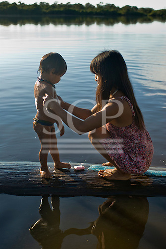 Xingu Indigenous Park, Mato Grosso State, Brazil. Aldeia Tres Irmaos (Kaiabi). Mother Ryeredrin Ikpeng and her son,morning  bathtime. Boatman Osmar's family.