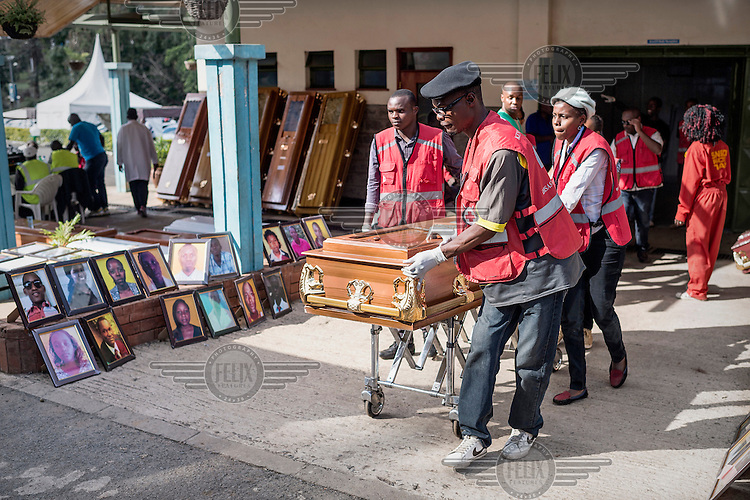 Staff wheel a coffin past a collection of photographs of murdered young students at the Chiromo morgue in Nairobi. The morgue is where the bodies of the students were taken following the Al-Shabaab attack on Garissa University campus during which 148 students and security personal died.