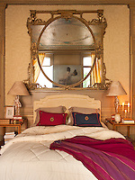 An elegant yellow bedroom with an ornate gilded mirror set above a double bed. A pair of lamps stand on matching bedside tables.