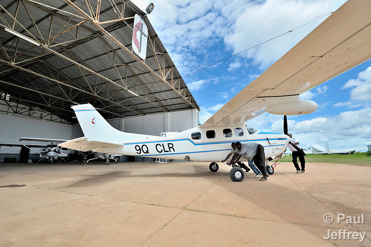 Rukang Chikomb (right), a pilot with the Wings of the Morning aviation ministry of The United Methodist Church, helps push a plane into the program's hanger in Lubumbashi, Democratic Republic of the Congo.