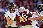 Wake Forest tight end Devin Pike, left, and tackle Dylan Intemann team up to block FSU defensive end Lorenzo Featherston in an NCAA football game in Tallahassee, FL October 4, 2014.  Florida State defeated Wake Forest 43-3.