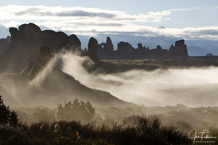 A ground fog swirls around the rock formations in Arches National Park, with Turret Arch in silhouette in the background, near Moab, Utah, USA.