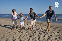 Family holding hands running together on beach (Licence this image exclusively with Getty: http://www.gettyimages.com/detail/83154269 )