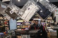 Commessa di un supermercato (G20) con mezzi di protezione antivirus . Alla cassa, sono esposte in vendita mascherine protettive