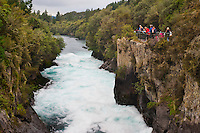 Tourist Visiting Huka Falls, Taupo, Waikato Region, North Island, New Zealand. The Huka Falls is an incredibly popular spot with tourists, just 4km outisde Taupo. The Waikato River narrows resulting in the thunderous Huka Falls, pouring over the final waterfall at 220,000 litres per second. There are a number of viewing platforms from which to be amazed by its power.