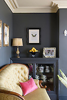 In the living room the walls and a built-in cupboard have been painted the same shade of graphite