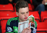 A young DSwansea supporter reads the match program prior to the Premier League match between Sunderland and Swansea City at the Stadium of Light, Sunderland, England, UK. Saturday 13 May 2017