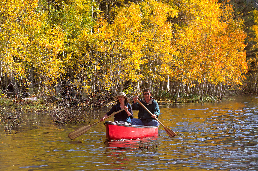A couple enjoy canoeing on GRANTS LAKE during autumns colorful display - GRANTS LAKE, CALIFORNIA (MR)