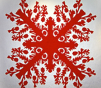 A beautiful red and white Hawaiian quilt with breadfruit pattern.