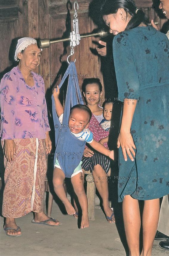 Indonesia; Java, mother and son during the posyandu (training program for the health of children),control of the weight of the newborn .Indonesia, Giava, mamma e bambino durante il posyandu (centri sanitari per la salute dei bambini), controllo del peso del neonato.