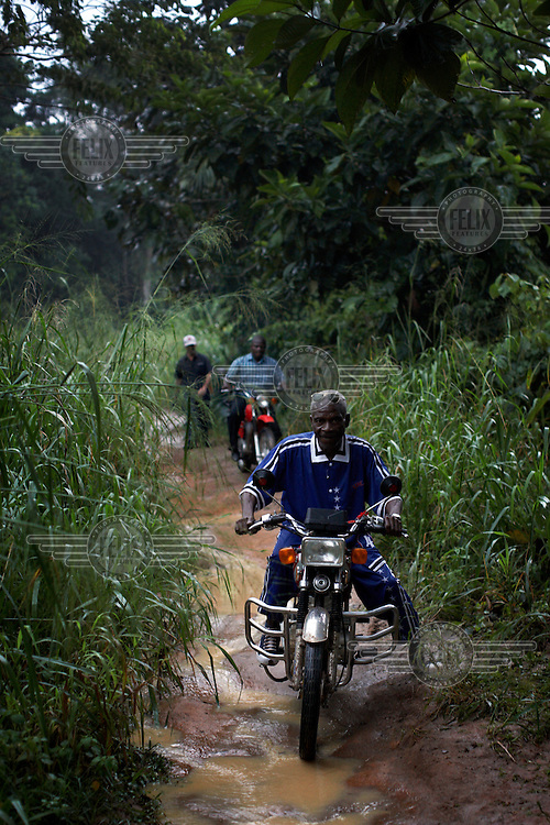 Riding becomes difficult as rain turns the trail into a stream. Motorbikes are necessary as the road deteriorates into a narrow trail sometimes no more than a foot wide.