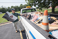 NWA Democrat-Gazette/J.T. WAMPLER Alfredo Franco, a code enforcement officer for Rogers, removes signs Monday Aug. 31, 2015 from near Dixieland Road. Monday is Franco's busiest day with lots of yard sale and event signs to collect.