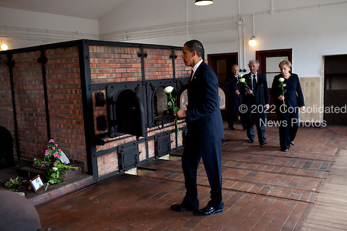 Buchenwald, Germany - June 5, 2009 -- United States President Barack Obama places a flower at a memorial at Buchenwald Nazi concentration camp, June 5, 2009.  With the President are Chancellor Angela Merkel of Germany, and camp survivors Elie Wiesel and Bertrand Herz. .Mandatory Credit: Pete Souza - White House via CNP