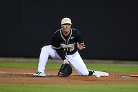 UCF Knights infielder James Vasquez (13) fields a throw in the dirt during the opening game of the season against the Siena Saints on February 13, 2015 at Jay Bergman Field in Orlando, Florida.  UCF defeated Siena 4-1.  (Mike Janes/Four Seam Images)
