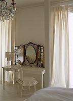 A gilded dressing-table mirror in a feminine bedroom with a serene white colour scheme