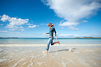 Female traveler runs through cold water of arctic beach, Gimsøy, Lofoten Islands, Norway
