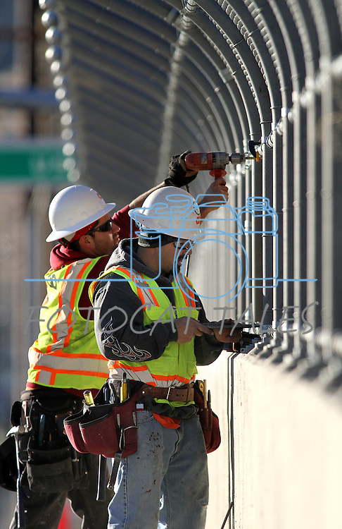 """Tony Ramirez, left, and Gabriel Delacerda, with Q&D Construction, install """"cattle drive image panels"""" on the Fairview overpass above the Highway 395 bypass on Monday afternoon in Carson City..Photo by Cathleen Allison"""