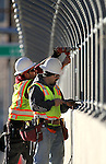 "Tony Ramirez, left, and Gabriel Delacerda, with Q&D Construction, install ""cattle drive image panels"" on the Fairview overpass above the Highway 395 bypass on Monday afternoon in Carson City..Photo by Cathleen Allison"