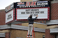 NWA Media/Michael Woods --12/23/2014-- w @NWAMICHAELW...Christopher Verdery with the UARK Ballroom changes out the buildings marquee Tuesday afternoon to wish people a haply holidays.  The ballroom is a popular place on Dickson Street for parities and events.