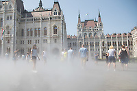 People cool down in the summer heat in the water sprays of a public square in front of the building of the Parliament in downtown Budapest, Hungary on Aug. 22, 2018. ATTILA VOLGYI