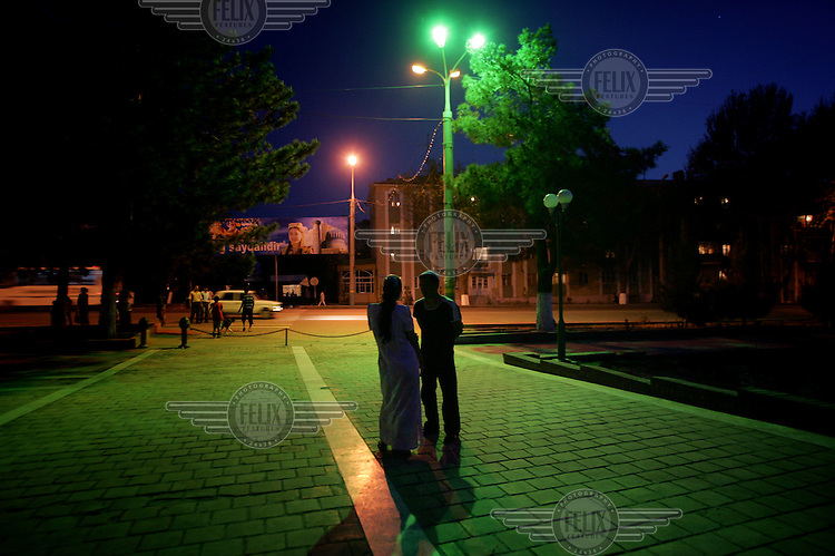 A young couple, lit by a street light, talk together in the city centre.