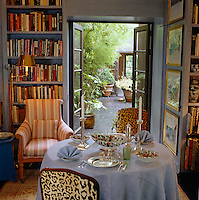 A table is laid for lunch in the small library where the French windows open onto a courtyard paved with slate and dominated by bamboo in tubs