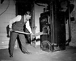Wilkinsburg PA:  View of Brady Stewart loading coal into the furnace at 1007 East End Avenue in Wilkinsburg - 1940.