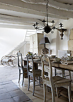 The long wooden farmhouse dining table is surrounded by 19th century Swedish chairs