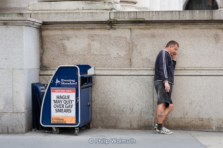 Man using a mobile phone by an Evening Standard billboard in the City of London