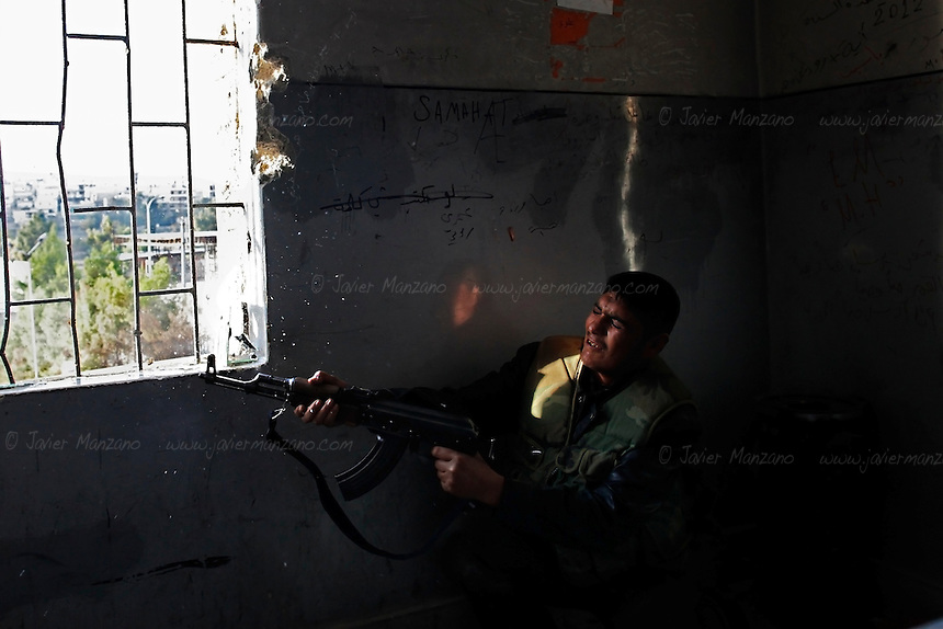 A Free Syria Army soldier fires at regime loyalist positions in the Bustan Al-Bashar neighborhood of Aleppo on the last day of a U.N.-negotiated seize fire that began on the first day of the Muslim holiday of Eid. Both sides exchanged small arms fire as the regime fired mortars throughout the day on several sectors of the city - the kurdish neighborhood of Ashrafya was also bombed by regime jets on October 29, 2012, following an FSA incursion in the district on Saturday...© Javier Manzano......................................................