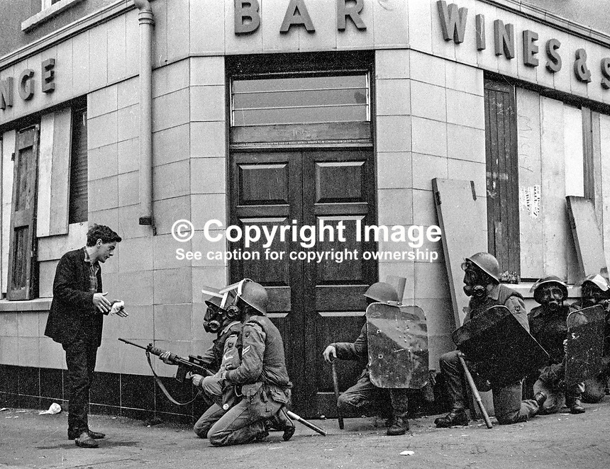 Soldiers in riot gear engage with a local youth. The British Army imposed during July 3 & 4, 1970, a 34 hour curfew (except for a two hour break to allow shopping) in approximately 50 streets in the Lower Falls district of Belfast, N Ireland, UK. A military helicopter hovered overhead warning people they would be arrested if they remained on the streets. An army search during the curfew uncovered 100 firearms, 100 home-made bombs, 250 lbs of explosives, 21000 rounds of ammunition and 8 two-way radios. This curfew is often seen as a turning point in souring relations between the Roman Catholic working class and the British Army. The army was no longer seen as the protector of the Catholic community. 197007030251...Copyright Image from Victor Patterson, 54 Dorchester Park, Belfast, UK, BT9 6RJ..Tel: +44 28 9066 1296.Mob: +44 7802 353836.Voicemail +44 20 8816 7153.Skype: victorpattersonbelfast.Email: victorpatterson@mac.com.Email: victorpatterson@ireland.com (back-up)..IMPORTANT: If you wish to use this image or any other of my images please go to www.victorpatterson.com and click on the Terms & Conditions. Then contact me by email or phone with the reference number(s) of the image(s) concerned.
