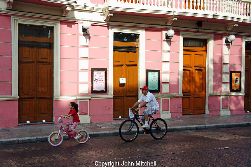 Father and young daughter  cyclists riding by a pink Spanish colonial building on Calle Sesenta, Merida, Yucatan, Mexico..