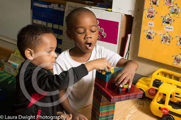 Preschool 3-4 year olds two boys playing together with vehicles on top of structure they made of magnetic plastic blocks
