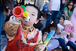 A pre-K boy in traditional dress blows a plastic horn at the Golden Dragon Parade for Chinese New Year, Chinatown, Los Angeles, CA