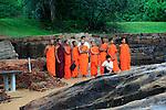 Orange robed monks, Gal Viharaya, UNESCO World Heritage Site, the ancient city of Polonnaruwa, Sri Lanka