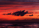 Dark dramatic clouds backlit by beautiful red sunset sky over lake Huron. Ontario, Canada. Pinery Provincial Park.