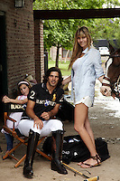 Nacho Figueras photographed with his wife and small daughter under the porch leading to the stableyard of their stud farm near Buenos Aires