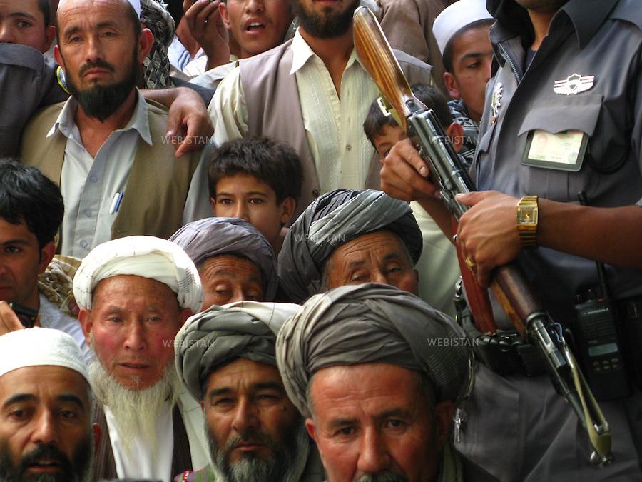 AFGHANISTAN - PROVINCE DE SAMANGAN - AYBAK - 5/08/2009 : Rassemblement de population, en majorite Ouzbek, venue ecouter et soutenir le Dr. Abdullah Abdullah, candidat aux elections presidentielles afghanes de 2009. .La foule est encadree par un policier afghan tenant a la main une Kalachnikov (AK 47)...AFGHANISTAN - SAMANGAN PROVINCE - AYBAK - 5/072009 : At a rally where mostly ethnic Uzbeks have gathered in support of  Dr. Abdullah Abdullah, candidate in the 2009 Afghan presidential elections..Supporters are closely guarded by an Afghan police officer holding a Kalachnikov (AK 47).