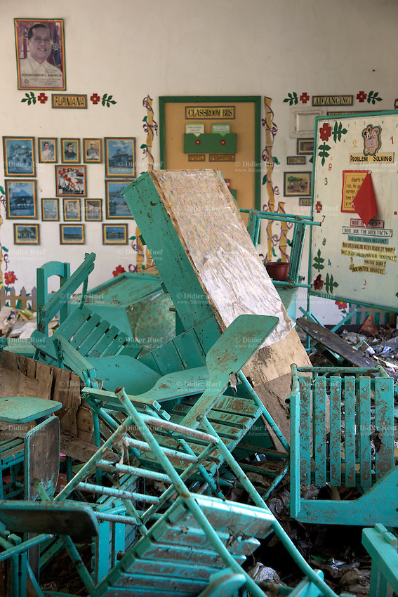 Philippines. Province Eastern Samar. Hernani. Central Elementary School. The building was destroyed and heavily flooded by typhoon Haiyan's winds and storm surge. Classroom. School's chairs and desks are dirty and messed up. A picture of Benigno Simeon Cojuangco Aquino III (born February 8, 1960), also known as Noynoy Aquino or PNoy, is a Filipino politician who has been the 15th President of the Philippines since June 2010. Typhoon Haiyan, known as Typhoon Yolanda in the Philippines, was an exceptionally powerful tropical cyclone that devastated the Philippines. Haiyan is also the strongest storm recorded at landfall in terms of wind speed. Typhoon Haiyan's casualties and destructions occured during a powerful storm surge, an offshore rise of water associated with a low pressure weather system. Storm surges are caused primarily by high winds pushing on the ocean's surface. The wind causes the water to pile up higher than the ordinary sea level. 26.11.13 © 2013 Didier Ruef